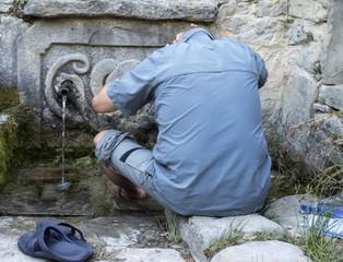 Hombre lavandose en una fuente de montaña