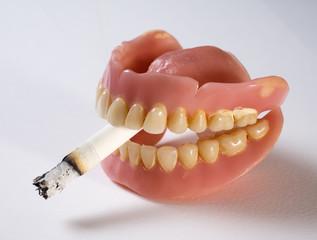 Dentadura postiza con un cigarrillo entre los dientes