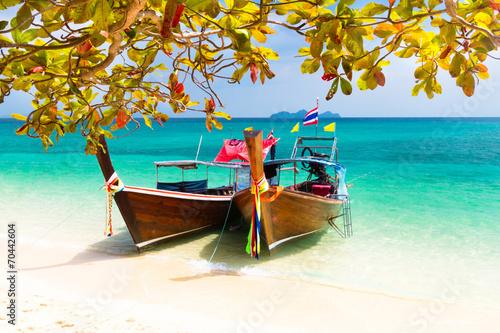 Leinwanddruck Bild Wooden boats on a tropical beach.