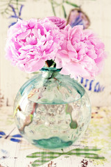 delicate pink peony flowers in a glass vase on the table.