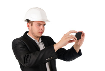 Man in a hardhat taking a photograph