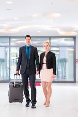 Paar bei Anreise in Hotellobby mit Koffer