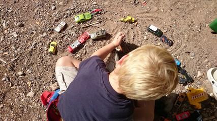 Niño rubio jugando con cochecitos