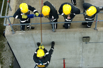 fire fighters abseiling down building
