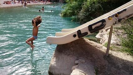 Niña saltando de tobogán al río