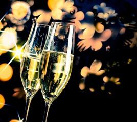 champagne flutes on golden and dark light background