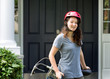 Teenage Girl wearing helmet while resting on bicycle outdoors ne