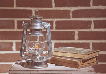 Burning kerosene lamp and books on brick wall background