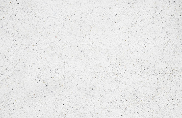 White cement wall with tiny rock on surface, grunge background.