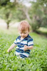 Toddler crawling in the garden and exploring backyard