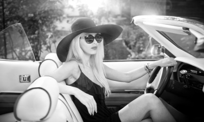 stylish blonde vintage woman driving a convertible retro car