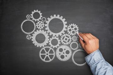 Cogwheels concept on blackboard