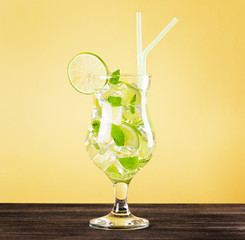 Glass of mojito cocktail on pastel yellow background