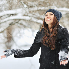 Woman playing with snow in a winter park