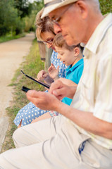 Grandchild and grandmother using a tablet outdoors