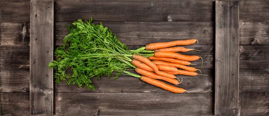 Fresh carrots over wooden background. Vegetable. Food