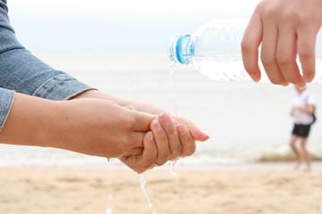 Bottled water splashing on hands.
