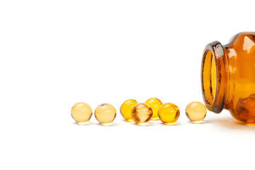 Oil vitamin capsule with bottle, white background