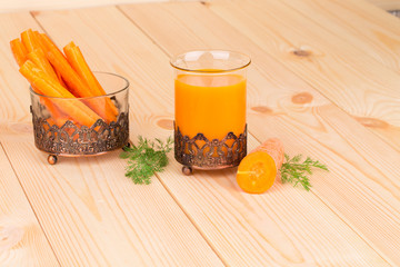 Fresh carrot juice on a wooden background.