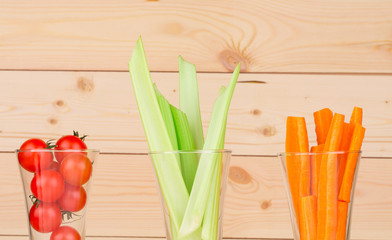 Fresh green celery with vegetables in glasses.