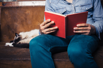 man reading on sofa with cat