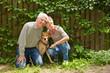 Paar Senioren mit Hund im Garten