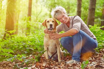 Ältere Frau mit Hund im Wald