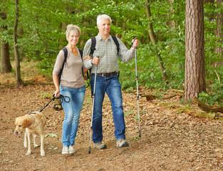 Paar Senioren beim Nordic Walking mit Hund