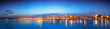 Leinwanddruck Bild - Panoramic sunset of cityscape with reflection in the sea