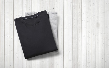 Two blank jumpers lying on white wood background