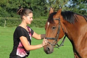 junge Frau beruhigt ihr Pferd