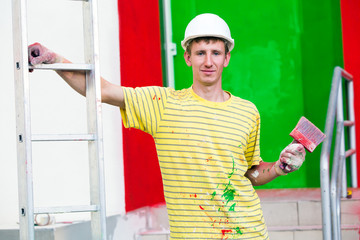 Painter with paintbrush and stepladder during decorating works