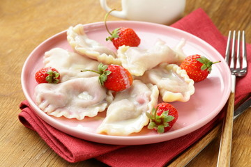 dumplings with berries and cream sauce with strawberries