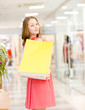 Happy young woman with shopping bags in a supermarket