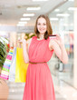 happy young woman with shopping bags showing credit card