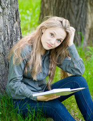 sad girl sitting on grass and reading a book