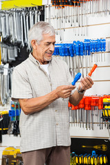 Customer Comparing Screwdrivers In Hardware Shop
