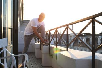 Sportler schnürt die Schuhe auf der Dachterrasse