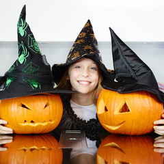 Cute girl as a witch with pumpkins