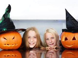 Cute girls with pumpkins in the kitchen