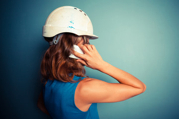 Young female builder on the phone