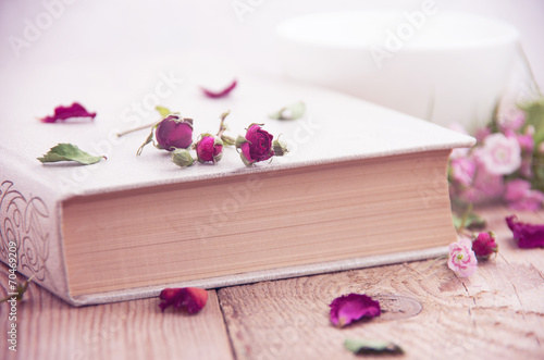 canvas print picture Dry roses and old book. Toned image