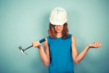 Young female builder with hammer