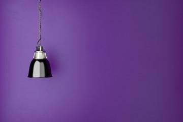 Lampe hängt vor lila Wand