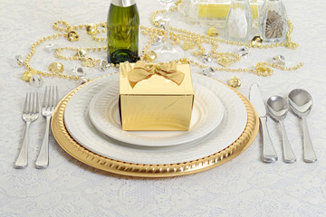 silver and gold table setting with present