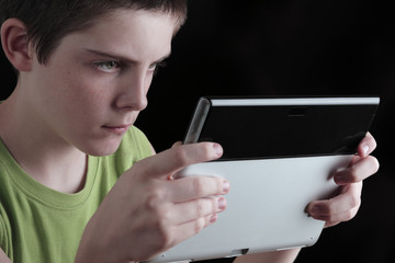 Teenage boy, holding tablet PC and intently looking at screen
