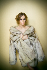 Attractive sexy young woman wearing a fur coat posing