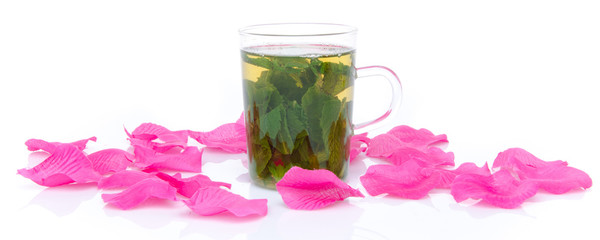 Cup of mint tea surrounded with pink petals