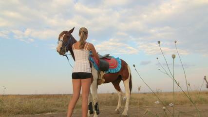 Girl rides a horse through the field