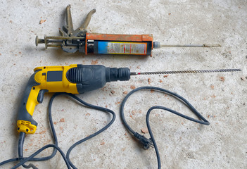 Construction Site: power drill with pistol cartridge resin.